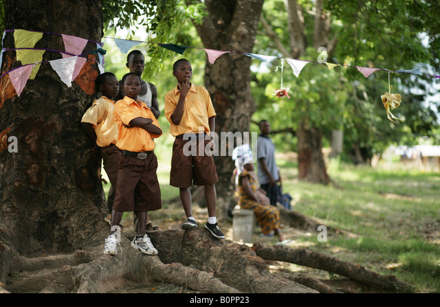 Boys in school uniforms standing a large tree - Stock Image