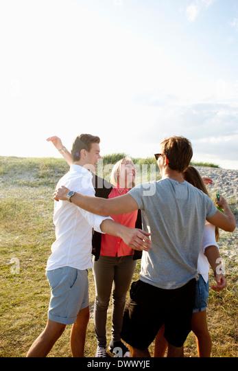 Cheerful friends enjoying at beach - Stock Image