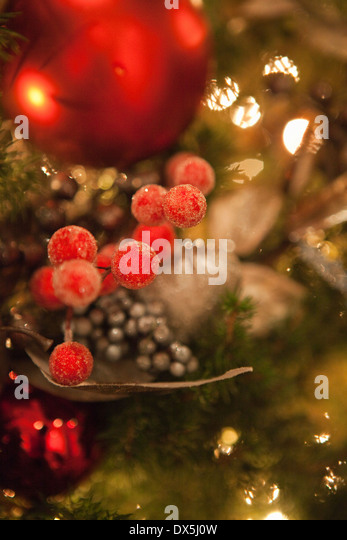 Berry and ball ornaments hanging in illuminated Christmas tree, close up - Stock Image