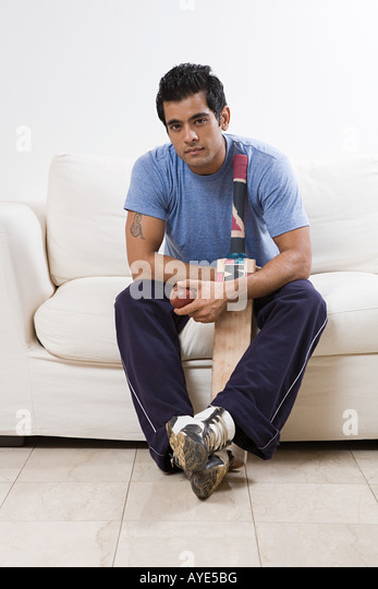 Portrait of a man holding a cricket bat - Stock Image