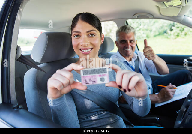 pretty woman has passed her driving test and holding driver's license - Stock Image