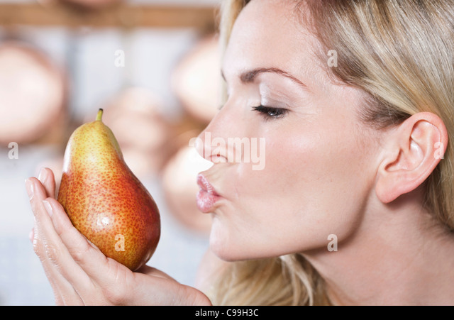 Italy, Tuscany, Magliano, Close up of young woman holding pear - Stock Image