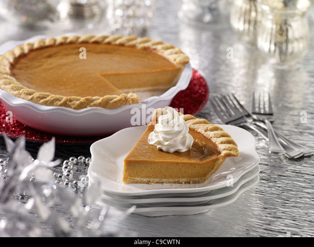 A pumpkin pie slice with a whole pie in the background in a holiday setting - Stock Image