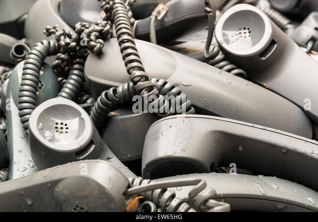 A skip full of electronic goods, mostly telephone sets, that have been stripped from a nearby office building. - Stock Image