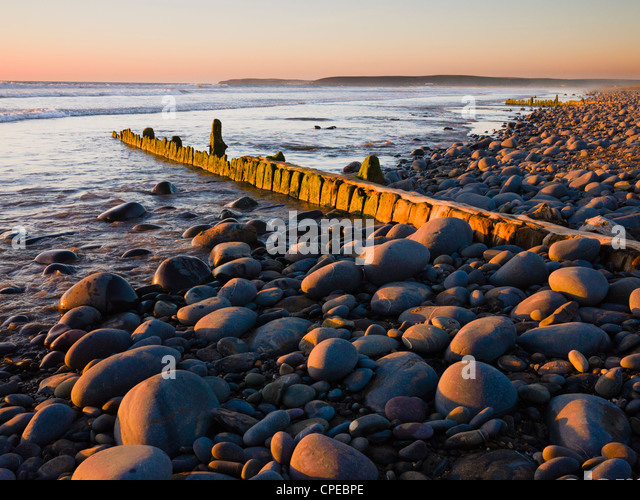 An old weathered groyne amongst the pebbles on Westward Ho! beach at sunset, Devon, England, United Kingdom. - Stock Image
