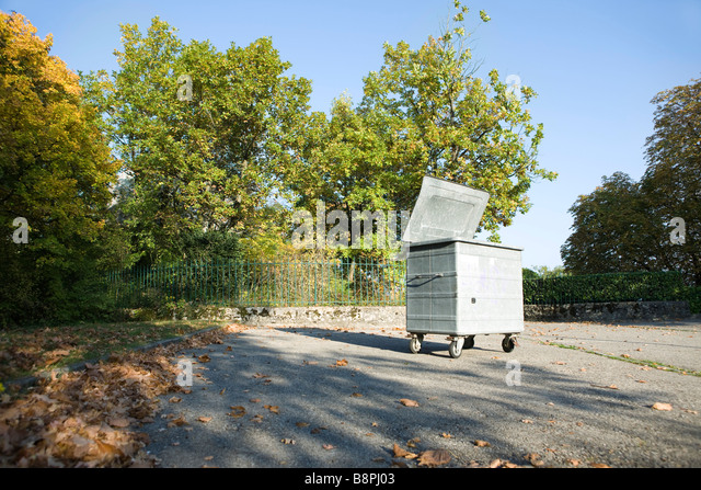 Small dumpster in parking lot at edge of wooded area - Stock Image