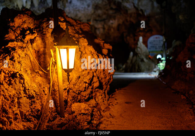 Illuminated Electric Lamp In Cave - Stock Image