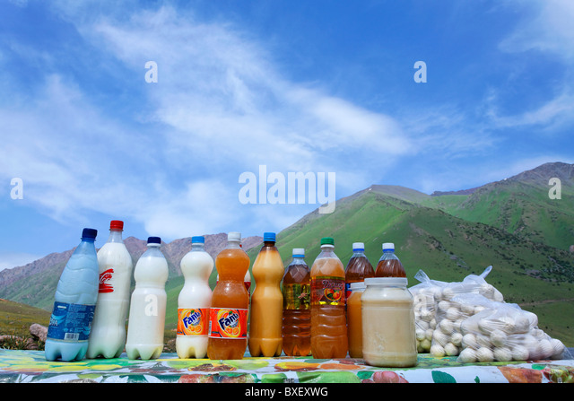 Kyrgyzstan - roadside market stalls selling dried milk balls and honey and mare's milk in recycled plastic bottles - Stock Image