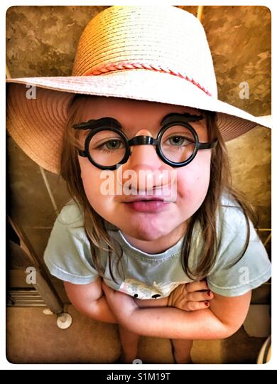 5 year old girl wearing a comedy nose and glasses. - Stock Image