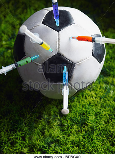 five syringes threaded in soccer ball. - Stock Image