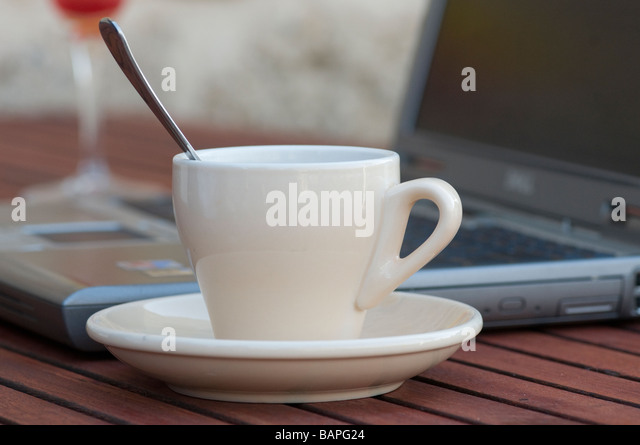 A cup of coffee and laptop - Stock Image
