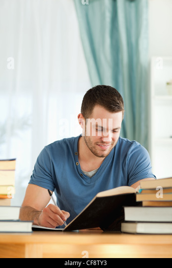 Smiling student reviewing his subject material - Stock Image