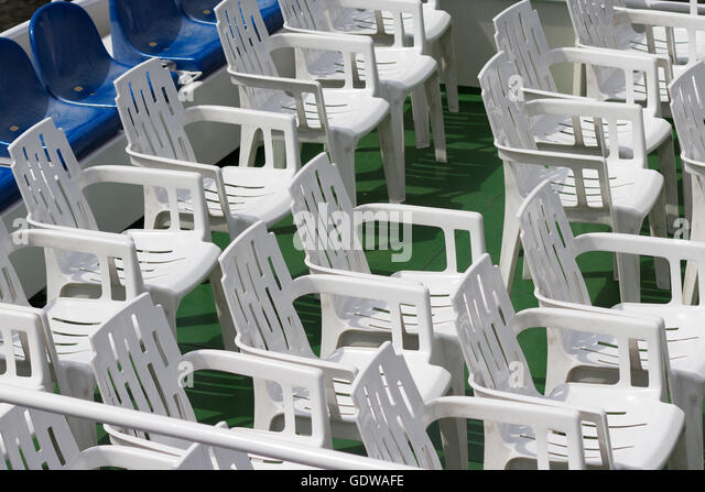 many  empty white plastic chairs in rows - Stock Image