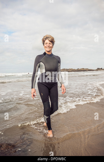 Mature female paddling on Devon coast, UK - Stock Image