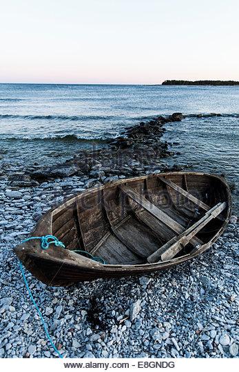 Wooden boat moored at seashore - Stock Image