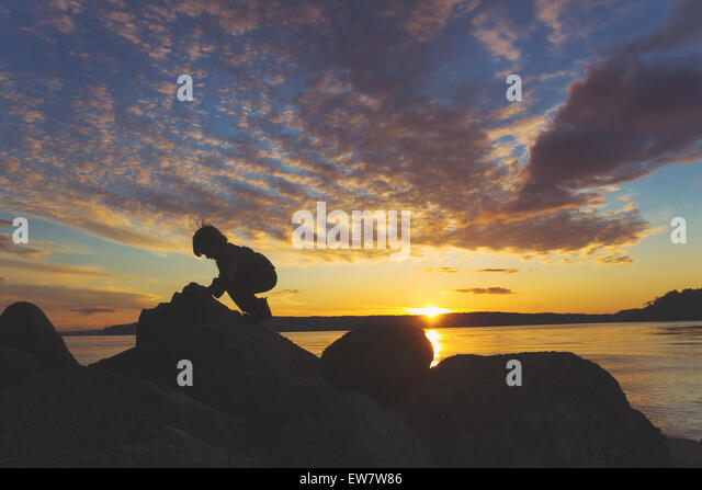 Silhouette of a boy climbing on rocks at the beach at sunset - Stock Image