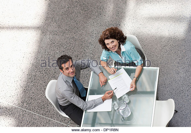 Businessman and businesswoman looking up - Stock Image
