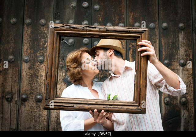 Portrait of adult son kissing mother on cheek, holding wooden frame in front of their faces, Mexico City, Mexico - Stock-Bilder