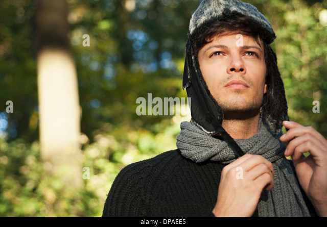 Portrait of man wearing hat and scarf, looking away - Stock Image