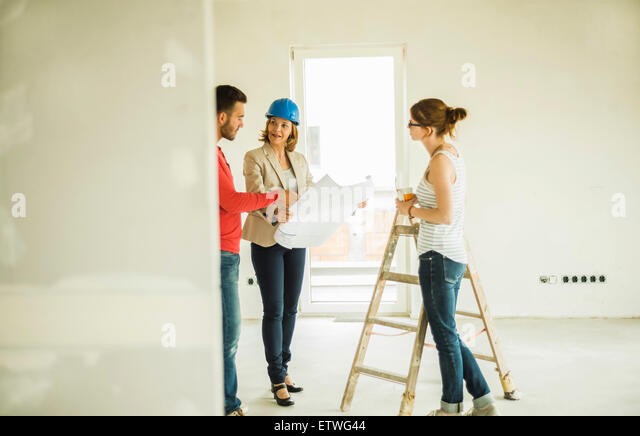 Architect showing construction plan to young couple - Stock-Bilder