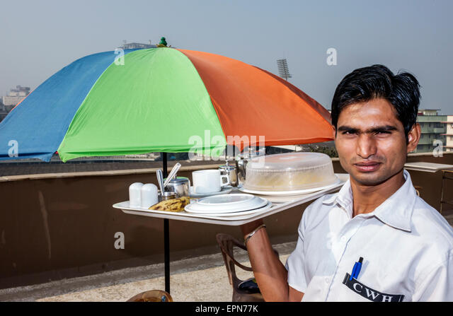 India Asian Mumbai Churchgate Chateau Windsor hotel man waiter serving job employee breakfast rooftop terrace - Stock Image
