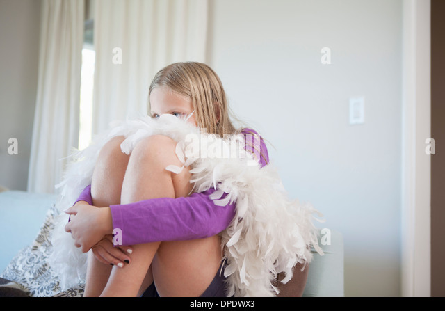 Portrait of girl sitting hugging knees and hiding face - Stock Image
