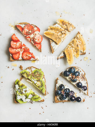Healthy breakfast wholegrain toasts with cream cheese, various fruit, seeds and nuts. Top view, grey marble background. - Stock Image