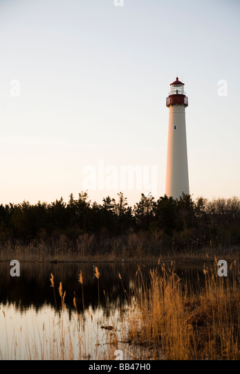 A lighthouse towers above a small lagoon and surrounding trees on the coast, New Jersey. - Stock Image