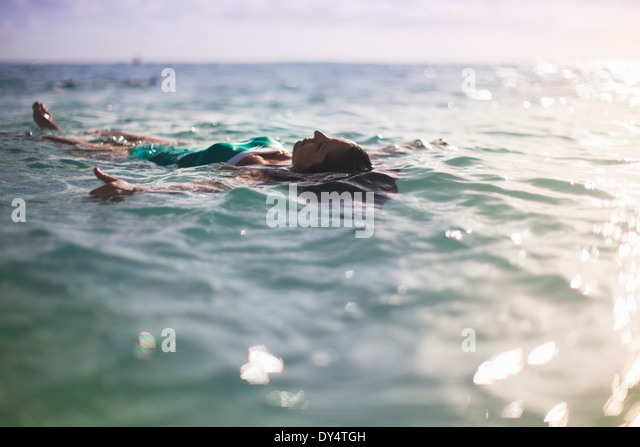 Woman floating on back in sea - Stock Image