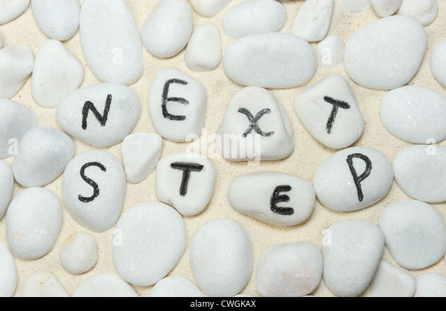 Next step words on group of pebbles - Stock Image