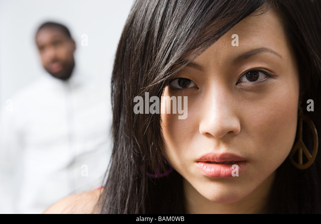Face of a woman with man in background - Stock Image