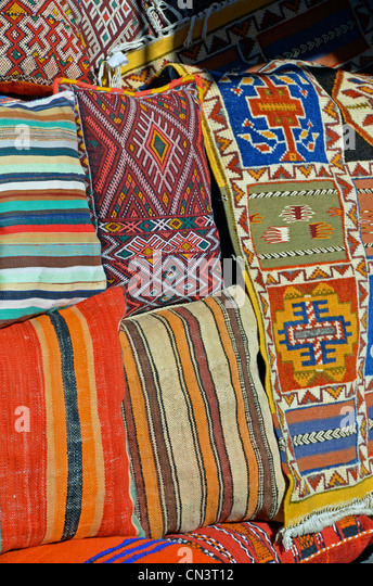Bright rugs and cushions, Moroccan souk - Stock Image