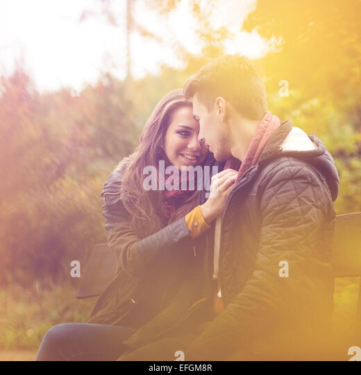 Couple of colorful autumn forest, sitting on a bench - Stock Image
