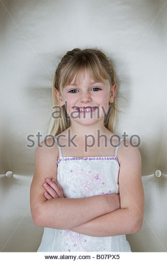 Little girl with folded arms wearing a party dress - Stock Image