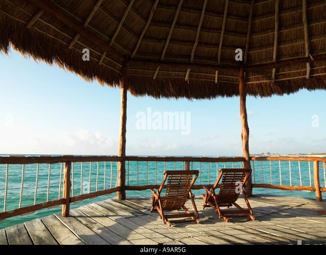 Mexico Quintana Roo Yucatan Peninsula Akumal Mayan Riviera two deck chairs under a palapa with a view of the sea - Stock Image