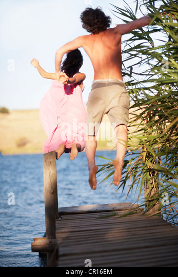 Couple jumping off dock into lake - Stock Image