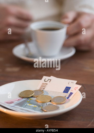 Euros on plate at cafe - Stock Image