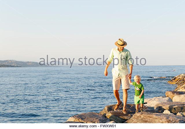 France, Provence-Alpes-Cote d´Azur, Saint Tropez, Man walking with son along rocky coast - Stock Image