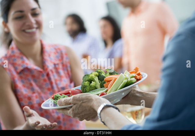 salad buffet of mixed ages and ethnicities meeting together - Stock Image