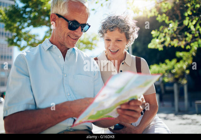 Elderly couple sitting outdoors and using city map. Happy retired couple looking for a destination on a city map. - Stock-Bilder