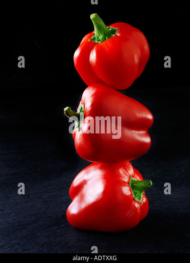 3 red peppers balanced on top of each other against a black background - Stock Image