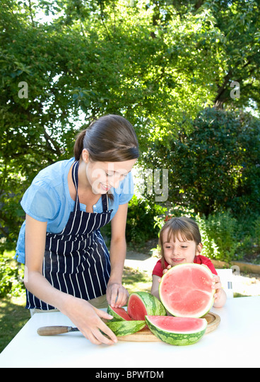 Mother and daughter prepare water melon - Stock Image
