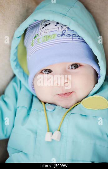 baby in blue jacket smiling at the camera - Stock Image