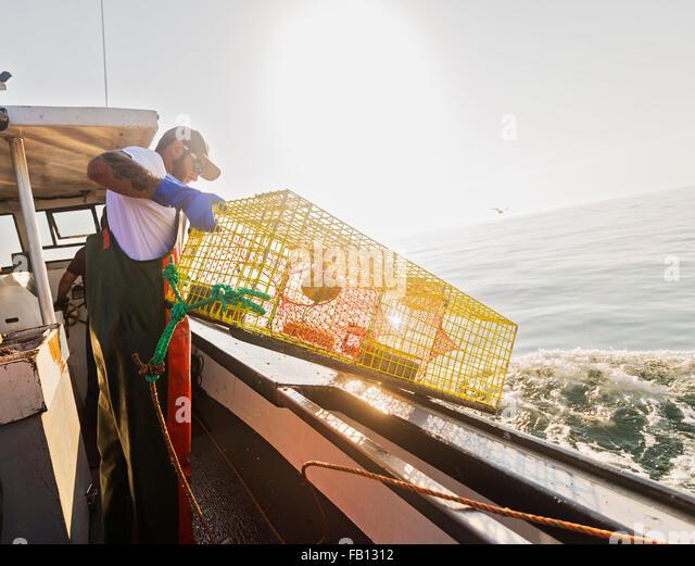 Fishermen throwing lobster trap - Stock Image