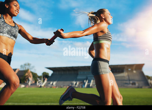 Female athletes passing over the baton while running on the track. Young women run relay race, track and field event. - Stock Image