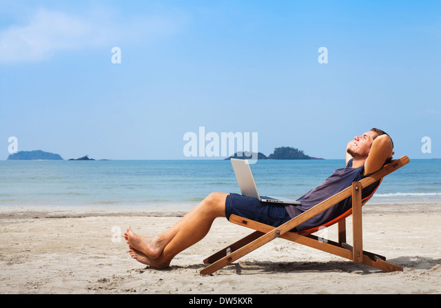 happy business man with laptop relaxing on the beach - Stock-Bilder