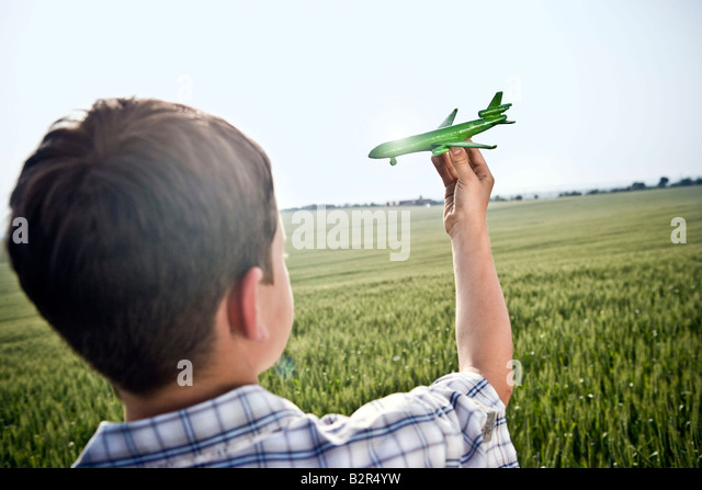 Boy playing with toy plane - Stock-Bilder