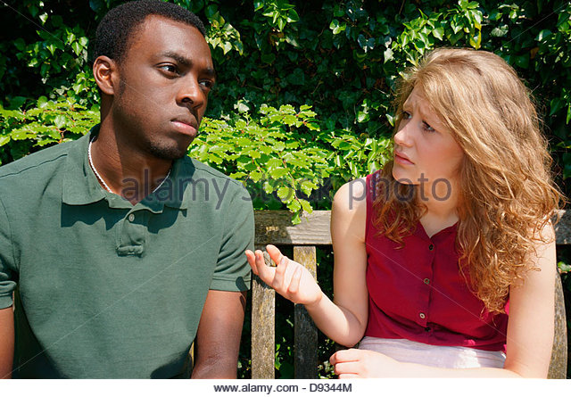 Sad or disappointed teenage couple, sitting on a bench outside in the sunshine, with the girlfriend explaining her - Stock Image