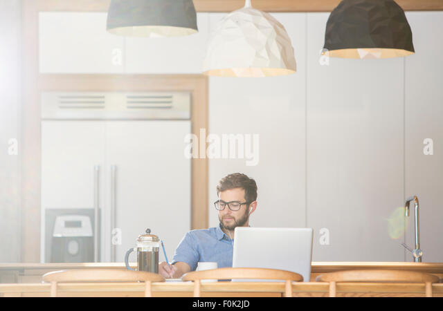 Man writing at laptop in kitchen with French press coffee - Stock Image