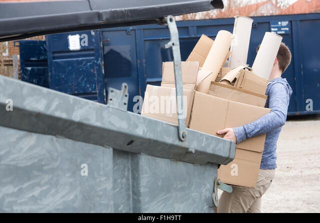 Teenage boy carrying cardboard waste to recycling bin - Stock Image